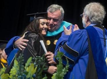 Boston Police Commissioner Edward Davis hugged his daughter Kaitlyn after she received her diploma from Suffolk University Sunday. The school graduated 1,175 students.